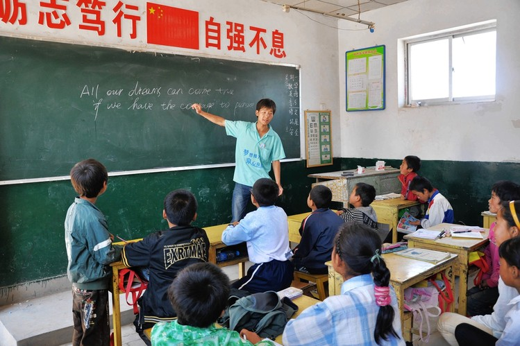 A Chinese teacher gives an English lesson to students in the Gansu province of northwest China in July 2013. Some have predicted that Mandarin Chinese will eventually become the world's language, but its elaborate tones are too difficult to learn beyond childhood.