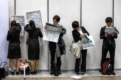 Estudantes universitários leem informações sobre as empresas participantes de uma feira de emprego a que eles compareceram em Tóquio, em março deste ano.