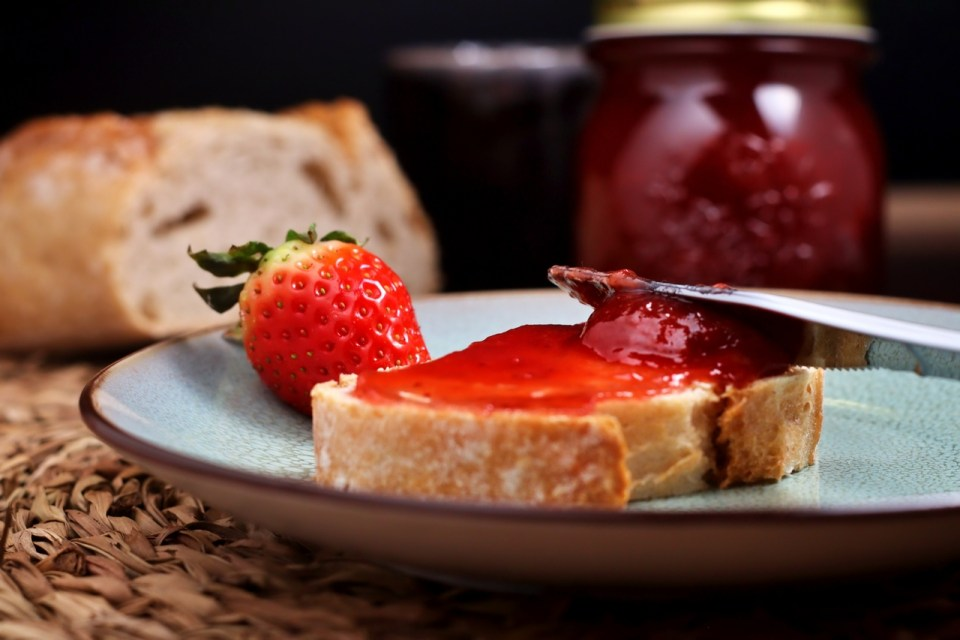 spreading strawberry preserves on bread