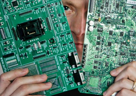 Security researcher Charlie Miller holds two automobile electronic control module circuit boards while posing in his home-office in Wildwood, Missouri