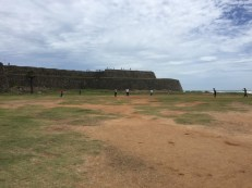 Boys playing cricket by the old fort walls