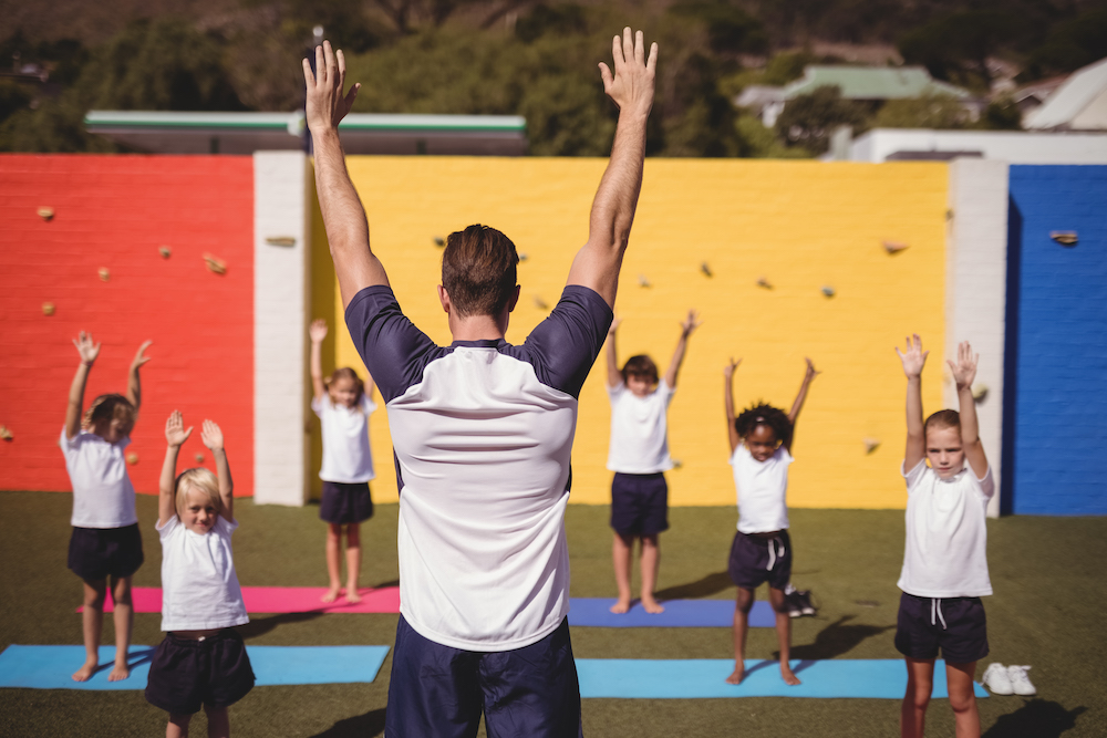 Coach teaching exercise to school kids in schoolyard