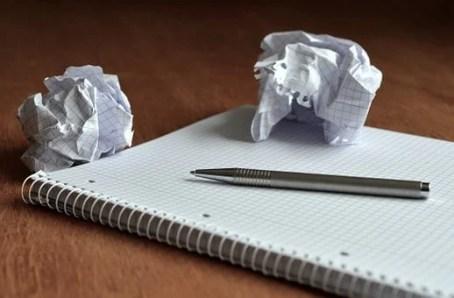 papel, caneta e bloco de notas amassados
