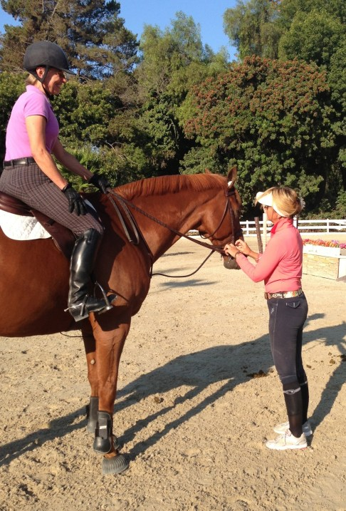 Devon back in action at Miraleste LLC at Sea Horse Riding Club, doing what she loves best, next to riding, of course – teaching. Shown here: adjusting Greg's bridle for Linda Swanson. Photo courtesy of Carrie Silvano