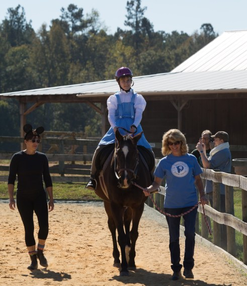 Lina (as Dorothy) and Ruby competing at NCTRC's Fall Festival and Horse Show. Bobbi Spinnenweber, Ruby's owner, leads while Lynn Norton-Ramirez, whose son also rides at NCTRC, volunteers as a sidewalker. (Photo by Jonathan Van Ark)