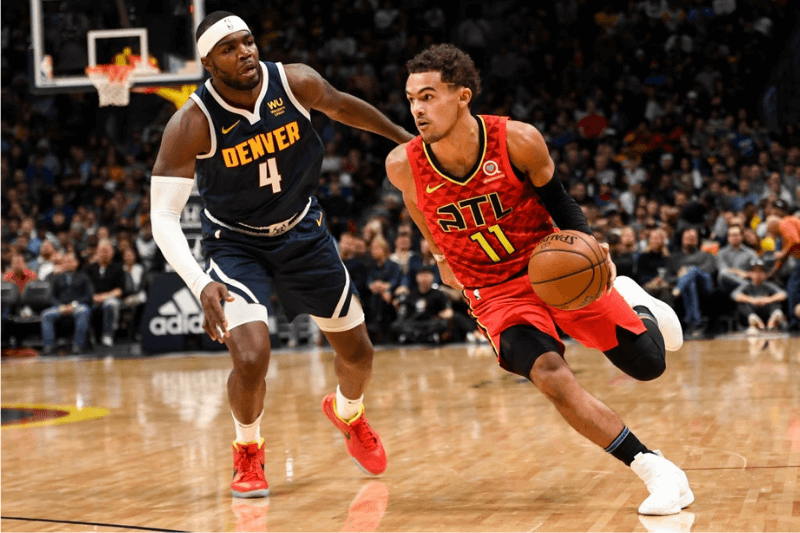 DENVER, CO - NOVEMBER 12: Trae Young (11) of the Atlanta Hawks drives on Paul Millsap (4) of the Denver Nuggets during the third quarter on Tuesday, November 12, 2019.