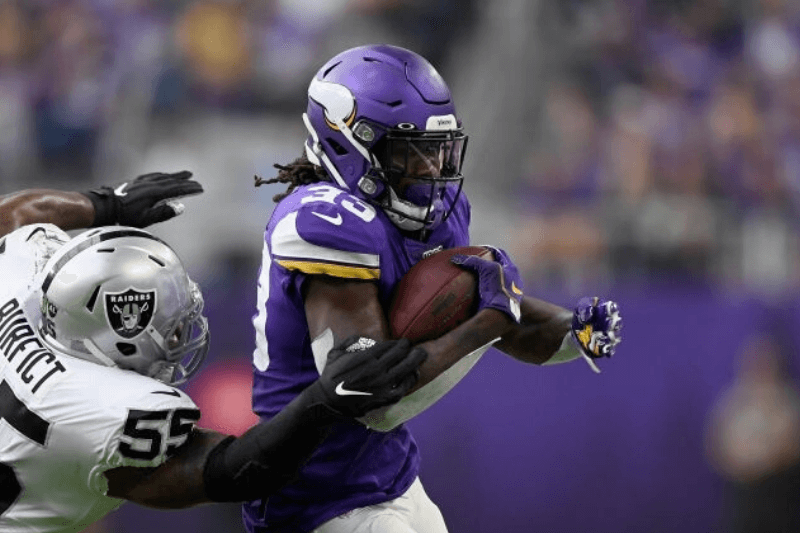 MINNEAPOLIS, MINNESOTA - SEPTEMBER 22: Dalvin Cook #33 of the Minnesota Vikings avoids a tackle by Vontaze Burfict #55 of the Oakland Raiders during the second quarter of the game at U.S. Bank Stadium on September 22, 2019 in Minneapolis, Minnesota.