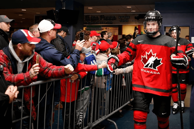 VICTORIA , BC - DECEMBER 19: Alexis Lafrenière #22 of Team Canada high fives with fans prior to a game versus Team Switzerland at the IIHF World Junior Championships at the Save-on-Foods Memorial Centre on December 19, 2018 in Victoria, British Columbia, Canada. Canada defeated Switzerland 5-3.