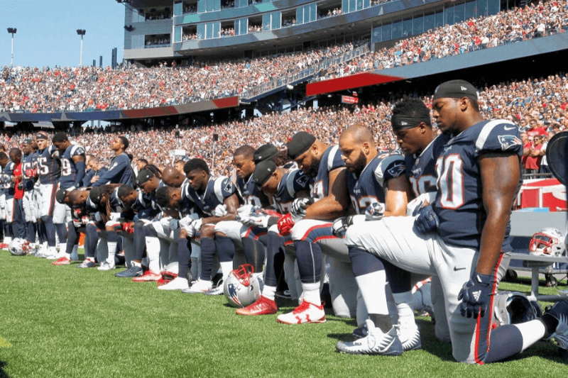 FOXBORO, MA - SEPTEMBER 24: Members of the New England Patriots kneel during the National Anthem before a game against the Houston Texans at Gillette Stadium on September 24, 2017 in Foxboro, Massachusetts.