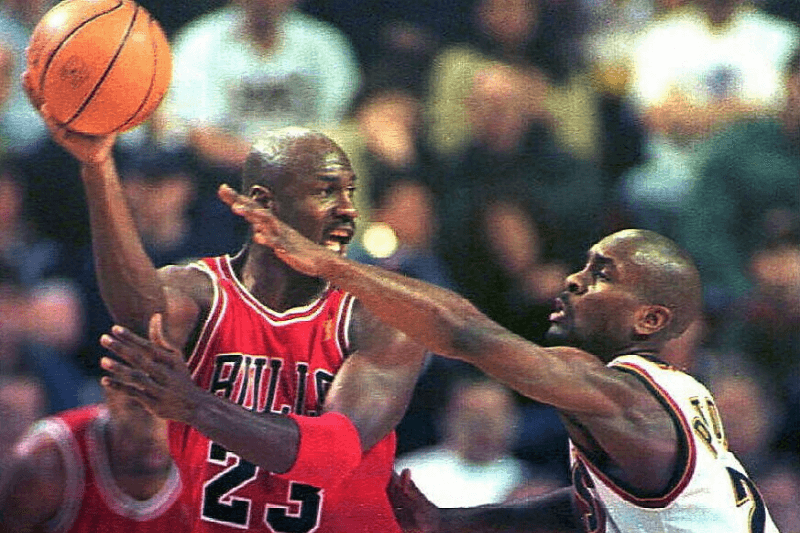 SEATTLE, UNITED STATES: Michael Jordan of the Chicago Bulls (L) looks to pass the ball as Seattle SuperSonics defender Gary Payton guards him during first quarter action in their game 03 February in Seattle, Washington. It was the first game between the two teams since the 1996 NBA Finals. Chicago won 91-84 with Jordan scoring 45 points.