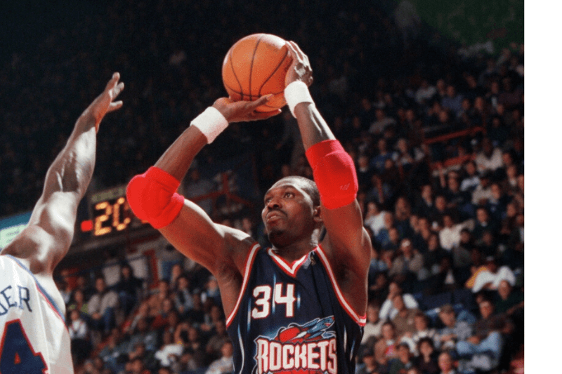 November 30, 1996; Landover, MD; FILE PHOTO: Houston center Hakeem Olajuwon (#34) shoots a jumper over Washington's Chris Webber (#4), at the USAir Arena.