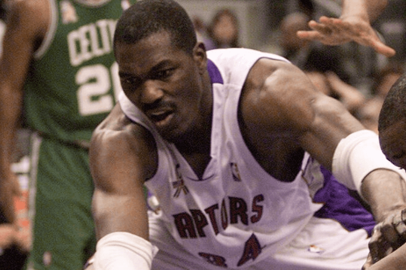 RAPTORS02--12/02/01----Hakeem Olajuwon chases a loose ball on the floor with Antione Walker. The Toronto Raptors had a rough afternoon versus the Boston Celtics in Toronto, December 2, 2001. The Raptors lost 85-69. The raptors only scored nine points in the fourth quarter and shot 31.8 percent from the field.