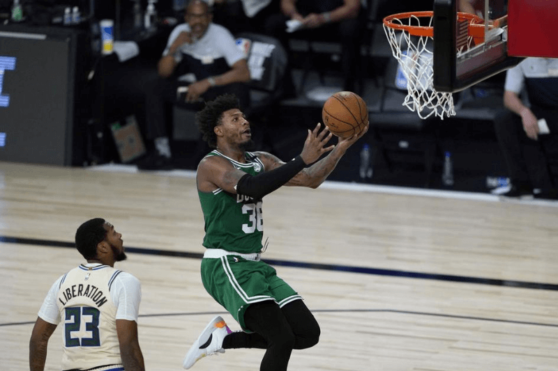 July 31, 2020; Lake Buena Vista, USA; Boston Celtics' Marcus Smart, right, heads to the basket past Milwaukee Bucks' Sterling Brown (23) during the second half of an NBA basketball game Friday, July 31, 2020, in Lake Buena Vista, Fla.