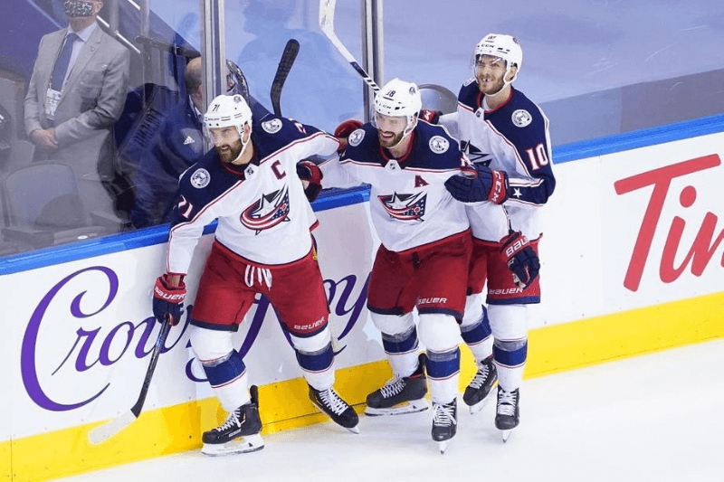 TORONTO, ONTARIO - AUGUST 09: Nick Foligno #71 of the Columbus Blue Jackets celebrates his empty net goal at 19:37 with Boone Jenner #38 and Alexander Wennberg #10 against the Toronto Maple Leafs in Game Five of the Eastern Conference Qualification Round prior to the 2020 NHL Stanley Cup Playoffs at Scotiabank Arena on August 09, 2020 in Toronto, Ontario