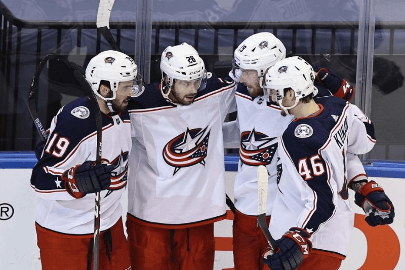 TORONTO, ONTARIO - AUGUST 11: The Columbus Blue Jackets celebrate a goal by Oliver Bjorkstrand #28 (2nd from left) against the Tampa Bay Lightning at 19:12 of the second period in Game One of the Eastern Conference First Round during the 2020 NHL Stanley Cup Playoffs at Scotiabank Arena on August 11, 2020 in Toronto, Ontario, Canada.