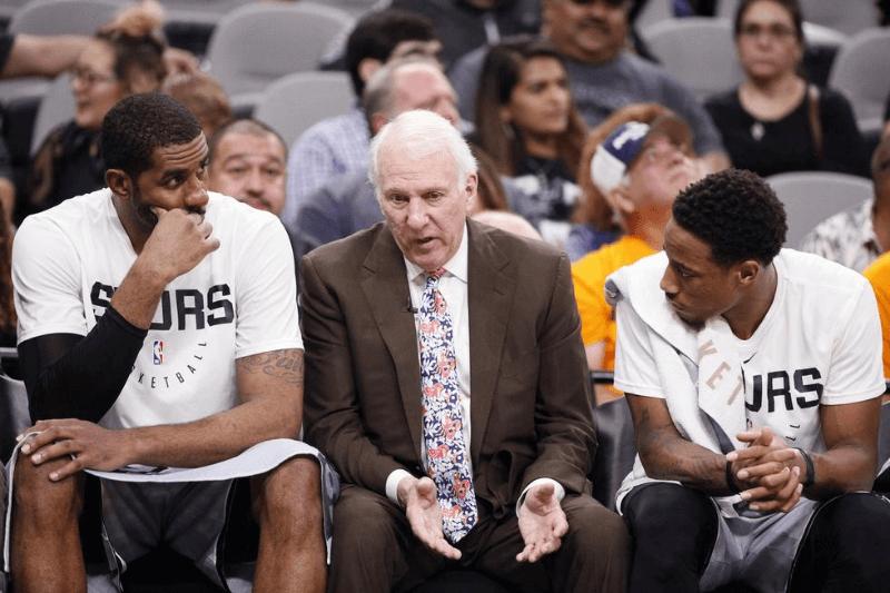 Nov 30, 2018; San Antonio, TX, USA; San Antonio Spurs head coach Gregg Popovich talks with LaMarcus Aldridge (left) as guard DeMar DeRozan (right) listens during the second half against the Houston Rockets at AT&T Center.