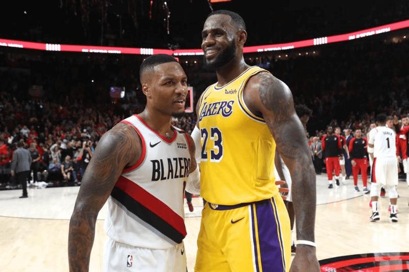 Oct 18, 2018; Portland, OR, USA; Portland Trail Blazers guard Damian Lillard (0) and Los Angeles Lakers forward LeBron James (23) hug after their game at Moda Center.
