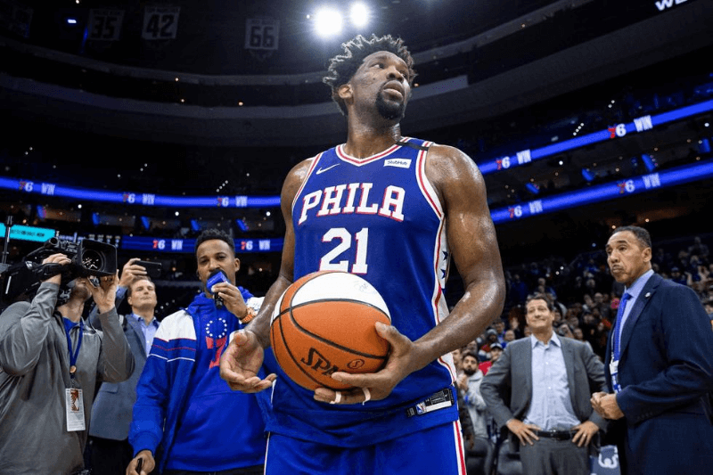 Feb 24, 2020; Philadelphia, Pennsylvania, USA; Philadelphia 76ers center Joel Embiid (21) prepares to throw the ceremonial game ball to fans after a victory against the Atlanta Hawks at Wells Fargo Center.