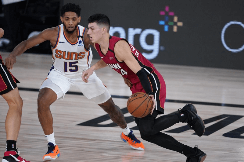 Aug 8, 2020; Lake Buena Vista, Florida, USA; Miami Heat's Tyler Herro (14) is defended by Phoenix Suns' Cameron Payne (15) during the second half of an NBA basketball game at Visa Athletic Center.