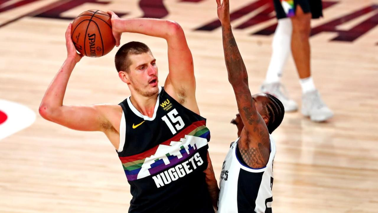 Sep 13, 2020; Lake Buena Vista, Florida, USA; Denver Nuggets center Nikola Jokic (15) handles the ball against LA Clippers guard Lou Williams (23) during the third quarter in game six of the second round of the 2020 NBA Playoffs at ESPN Wide World of Sports Complex. Mandatory Credit: Kim Klement-USA TODAY Sports