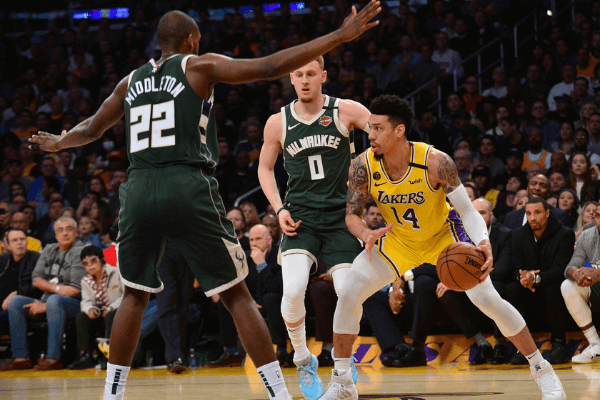 March 6, 2020; Los Angeles, California, USA; Los Angeles Lakers guard Danny Green (14) controls the ball against Milwaukee Bucks guard Donte DiVincenzo (0) and forward Khris Middleton (22) during the first half at Staples Center. Mandatory Credit: Gary A. Vasquez-USA TODAY Sports