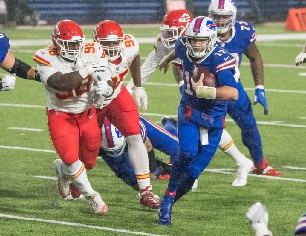 Buffalo Bills quarterback Josh Allen (17) outruns Kansas City Chiefs defensive tackle Tershawn Wharton (98) and defensive tackle Chris Jones (95) in the fourth quarter at Bills Stadium.