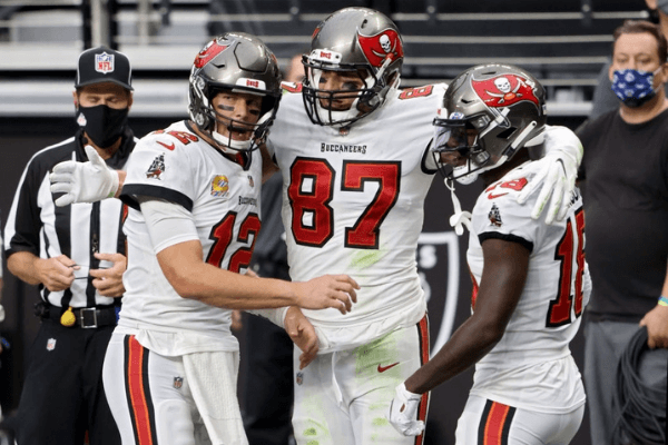 Tom Brady #12, Rob Gronkowski #87, and Tyler Johnson #18 of the Tampa Bay Buccaneers celebrate after scoring a touchdown in the second quarter against the Las Vegas Raiders at Allegiant Stadium on October 25, 2020 in Las Vegas, Nevada.