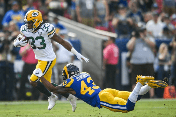 Strong safety John Johnson #43 of the Los Angeles Rams tackles running back Aaron Jones #33 of the Green Bay Packers in the first quarter at Los Angeles Memorial Coliseum on October 28, 2018 in Los Angeles, California.
