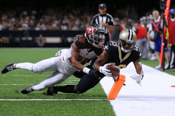 Michael Thomas #13 of the New Orleans Saints scores a touchdown as Vernon III Hargreaves #28 of the Tampa Bay Buccaneers defends during the first half of a game at the Mercedes Benz Superdome on October 06, 2019 in New Orleans, Louisiana.