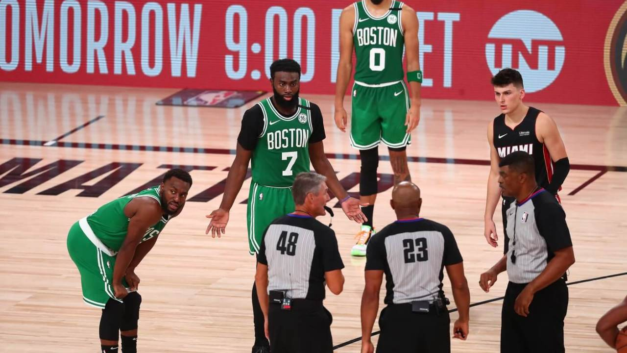 Sep 23, 2020; Lake Buena Vista, Florida, USA; Boston Celtics guard Kemba Walker (left) and guard Jaylen Brown (7) and forward Jayson Tatum (0) and Miami Heat guard Tyler Herro (right) look on as the official crew huddle after Walker was fouled during the second half of game four of the Eastern Conference Finals of the 2020 NBA Playoffs at AdventHealth Arena.