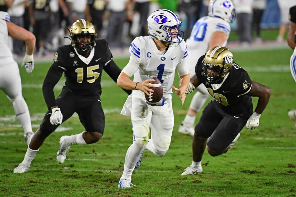 Brigham Young Cougars quarterback Zach Wilson (1) scrambles under pressure for UCF Knights linebacker Eriq Gilyard (10) and linebacker Tatum Bethune (15) during the first half at FAU Stadium.