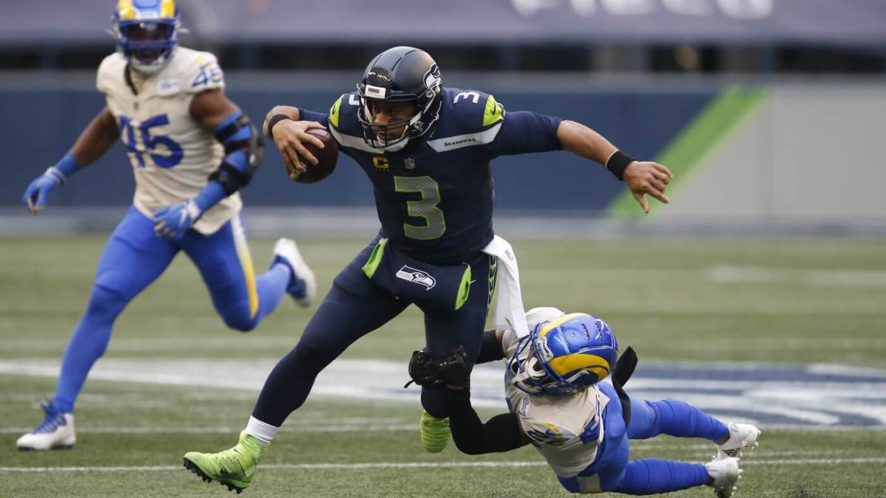 Seattle Seahawks quarterback Russell Wilson (3) runs the ball while Los Angeles Rams cornerback Troy Hill (22) defends during the second quarter at Lumen Field.