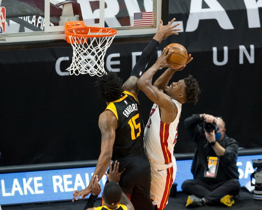 Miami Heat forward Jimmy Butler (right) shoots the ball against Utah Jazz center Derrick Favors (15) during the first half at Vivint Smart Home Arena.