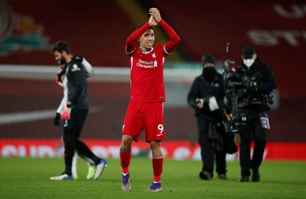 LIVERPOOL, ENGLAND - DECEMBER 16:  Roberto Firmino of Liverpool applauds the near 2000 crowd in the Kop after scoring a last minute winning goal during the Premier League match between Liverpool and Tottenham Hotspur at Anfield on December 16, 2020 in Liverpool, England. A limited number of fans (2000) are welcomed back to stadiums to watch elite football across England. This was following easing of restrictions on spectators in tiers one and two areas only. (Photo by Clive Brunskill/Getty Images)