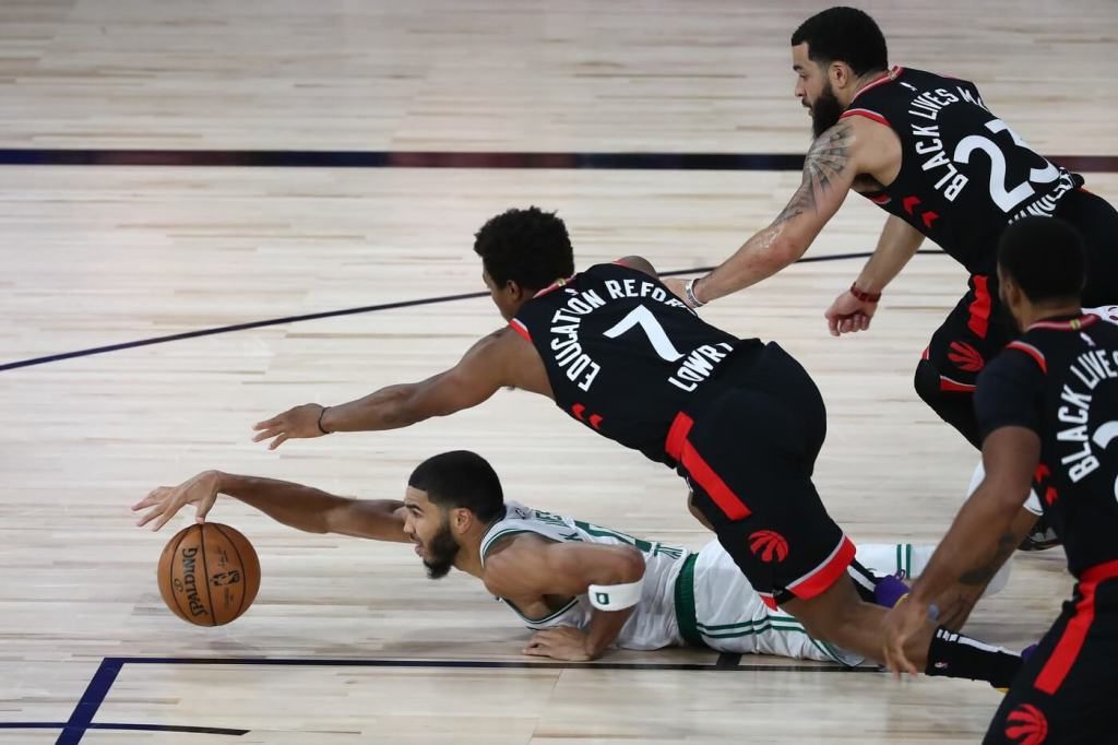 Sep 5, 2020; Lake Buena Vista, Florida, USA; Boston Celtics forward Jayson Tatum (on floor) chases a loose ball against Toronto Raptors guard Kyle Lowry (7) and guard Fred VanVleet (23) during the second half of game four in the second round of the 2020 NBA Playoffs at ESPN Wide World of Sports Complex. Mandatory Credit: Kim Klement-USA TODAY Sports