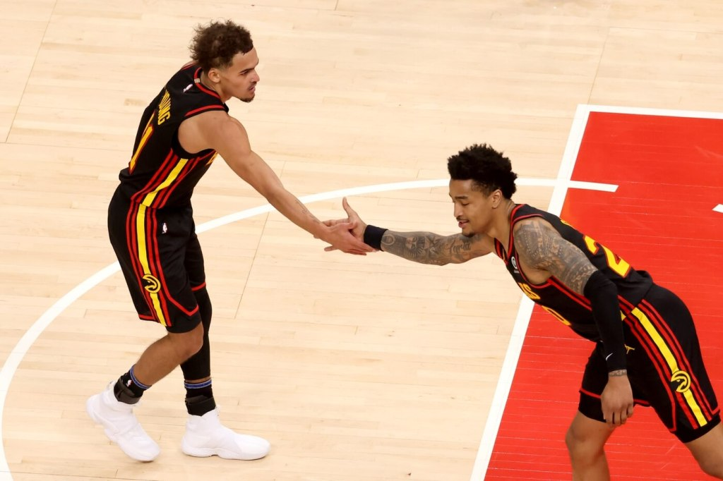 Feb 21, 2021; Atlanta, Georgia, USA; Atlanta Hawks point guard Trae Young (11) celebrates a play with forward John Collins (20) in the fourth quarter against the Denver Nuggets at State Farm Arena. Mandatory Credit: Jason Getz-USA TODAY Sports