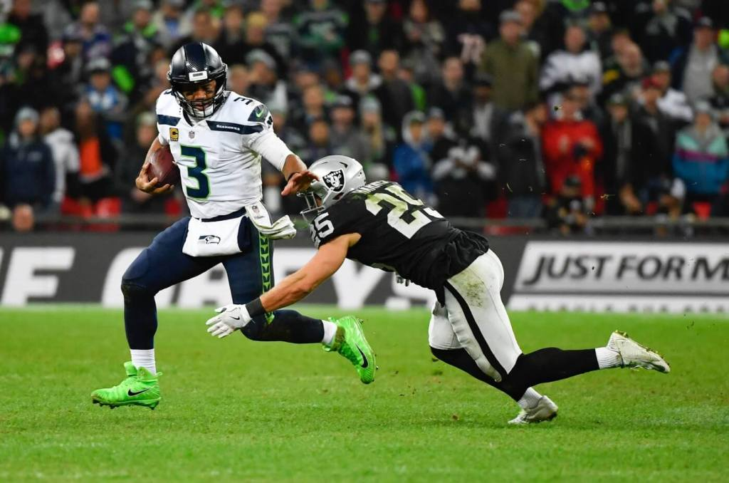 Oct 14, 2018; London, United Kingdom; Seattle Seahawks quarterback Russell Wilson (3) evades the tackle from Oakland Raiders defensive back Erik Harris (25) and runs for 9 yards during the fourth quarter of the game at Wembley Stadium. Mandatory Credit: Steve Flynn-USA TODAY Sports