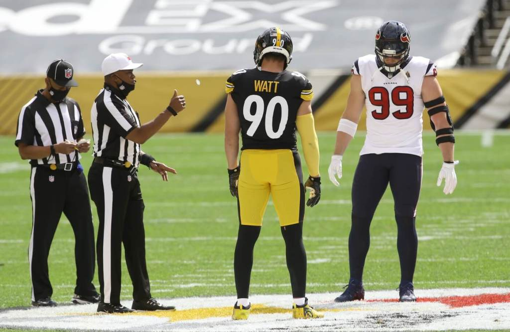 Sep 27, 2020; Pittsburgh, Pennsylvania, USA; NFL referee Shawn Smith (14) flips the coin as brothers Pittsburgh Steelers outside linebacker T.J. Watt (90) and Houston Texans defensive end J.J. Watt (99) take part before their game against at Heinz Field. The Steelers won 28-21. Mandatory Credit: Charles LeClaire-USA TODAY Sports