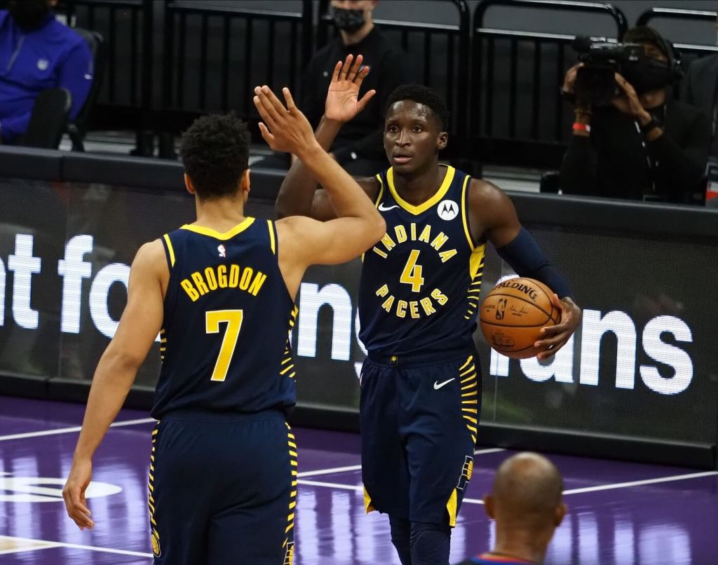 Jan 11, 2021; Sacramento, California, USA; Indiana Pacers guard Malcom Brogdon (7) high fives guard Victor Oladipo (4) after a play against the Sacramento Kings during the fourth quarter at Golden 1 Center. Mandatory Credit: Kelley L Cox-USA TODAY Sports