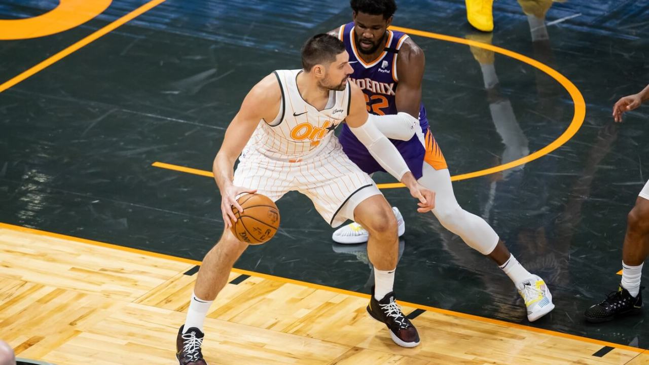 Mar 24, 2021; Orlando, Florida, USA; Orlando Magic center Nikola Vucevic (9) drives past Phoenix Suns center Deandre Ayton (22) during the fourth quarter of a game at Amway Center.
