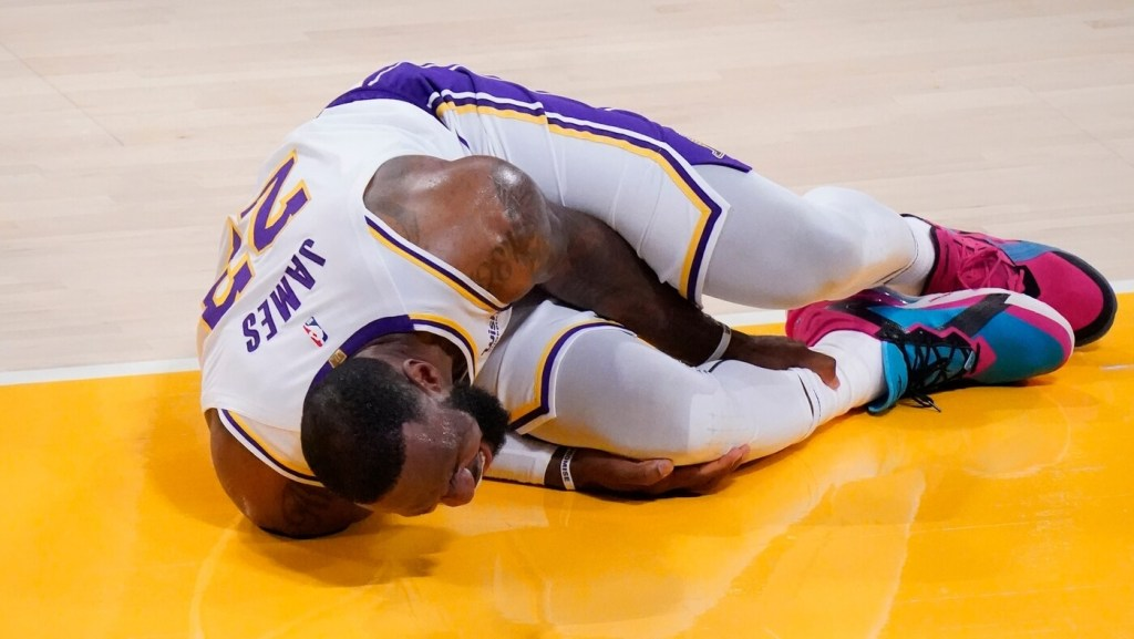 Mar 20, 2021; Los Angeles, California, USA; Los Angeles Lakers forward LeBron James (23) grabs his leg after a collision with an Atlanta Hawks player in the second quarter at Staples Center. Mandatory Credit: Robert Hanashiro-USA TODAY Sports