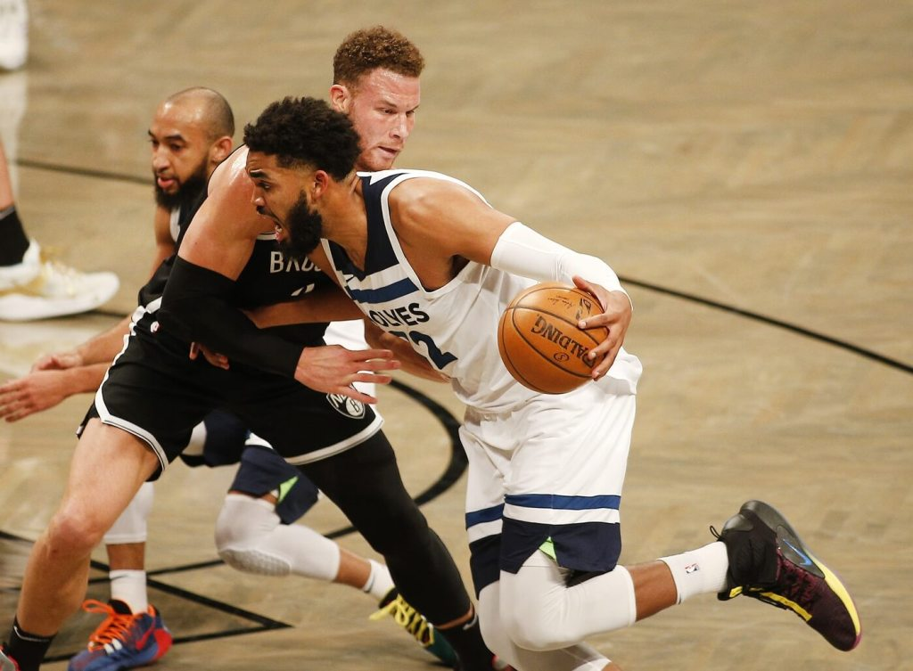 Mar 29, 2021; Brooklyn, New York, USA; Minnesota Timberwolves center Karl-Anthony Towns (32) dribbles the ball against Brooklyn Nets forward Blake Griffin (2) during the second half at Barclays Center. Mandatory Credit: Andy Marlin-USA TODAY Sports