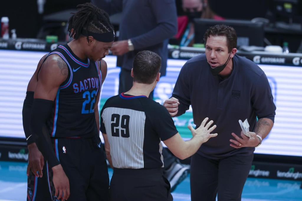 Mar 15, 2021; Charlotte, North Carolina, USA; Sacramento Kings coach Luke Walton argues with referee Mark Lindsay (29) as center Richaun Holmes (22) looks on during the fourth quarter against the Charlotte Hornets at Spectrum Center. The Charlotte Hornets won 122-116. Mandatory Credit: Nell Redmond-USA TODAY Sports