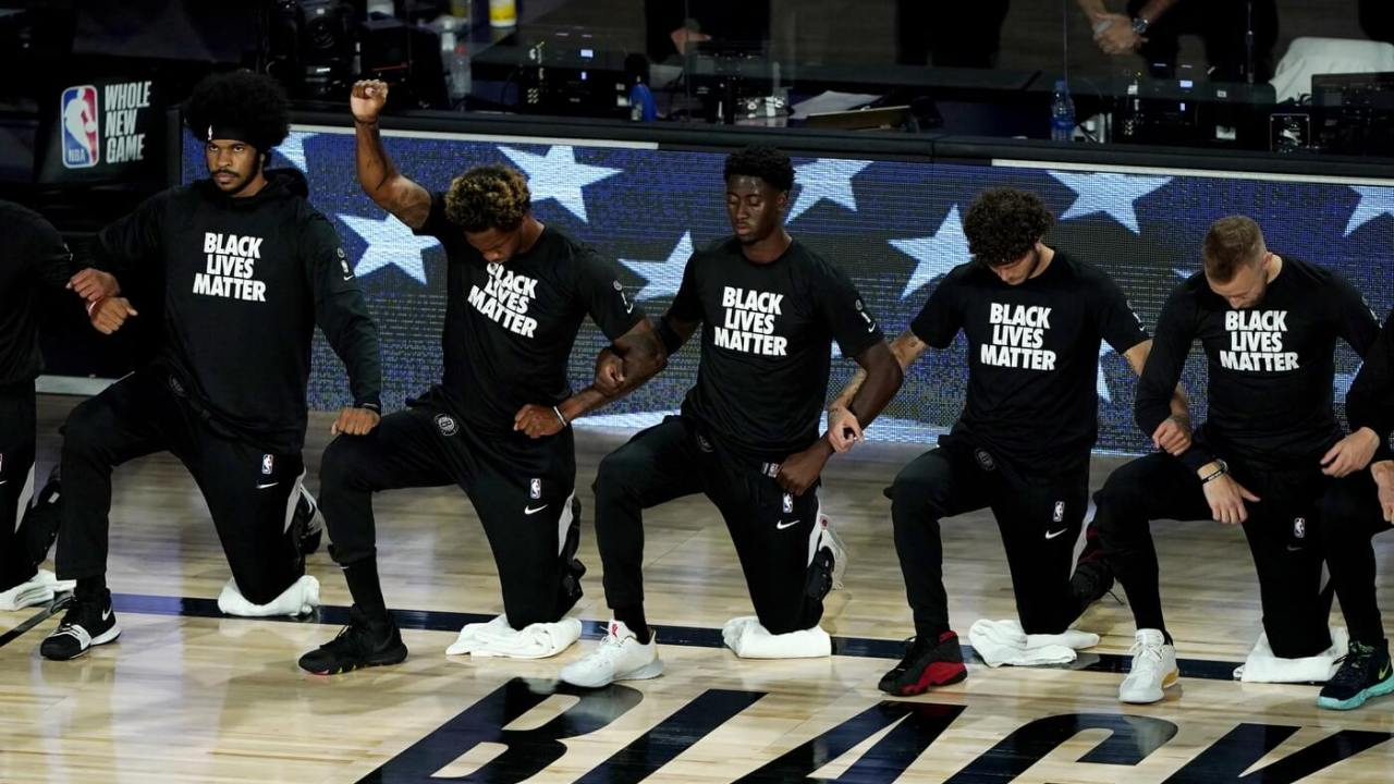 ooklyn Nets Lance Thomas, second from left, gestures as he and teammates kneel in honor of the Black Lives Matter movement prior to an NBA basketball game against the Portland Trail Blazers at ESPN Wide World of Sports Complex.