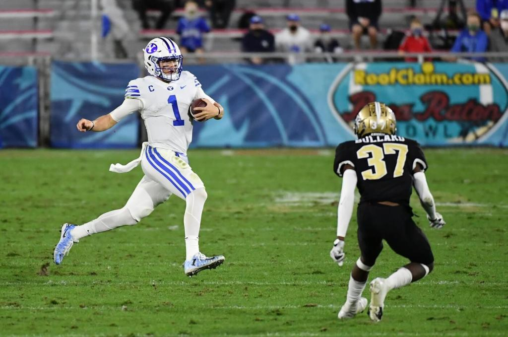 Brigham Young Cougars quarterback Zach Wilson (1) scrambles with the ball against the UCF Knights during the first half at FAU Stadium.