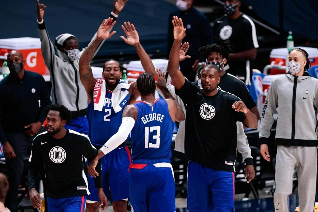 Dec 25, 2020; Denver, Colorado, USA; Los Angeles Clippers guard Paul George (13) celebrates with forward Serge Ibaka (9) and forward Kawhi Leonard (2) during a timeout in the third quarter against the Denver Nuggets at Ball Arena. Mandatory Credit: Isaiah J. Downing-USA TODAY Sports