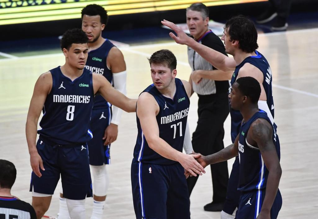 Apr 3, 2021; Washington, District of Columbia, USA; Dallas Mavericks guard Luka Doncic (77) is congratulated by teammates during the fourth quarter against the Washington Wizards at Capital One Arena. Mandatory Credit: Brad Mills-USA TODAY Sports