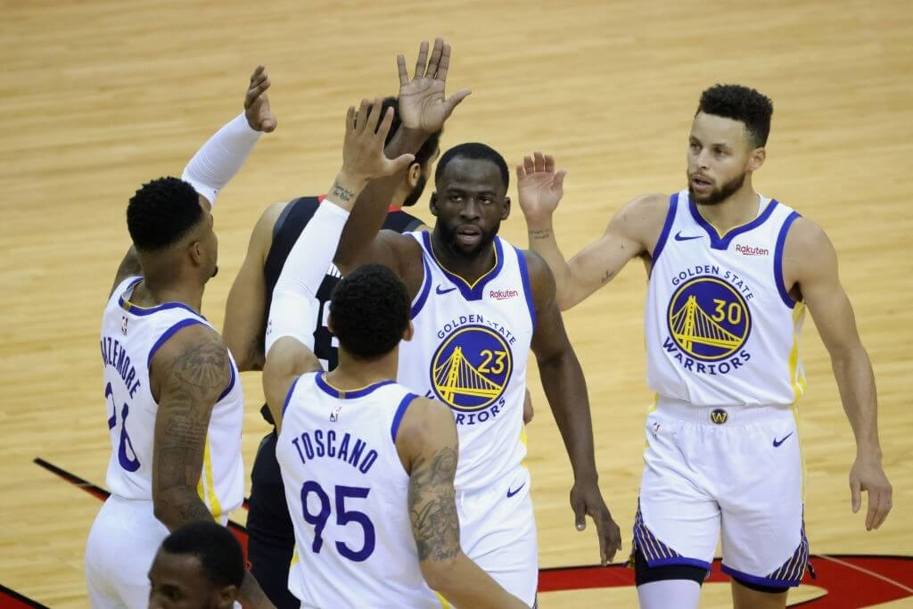 HOUSTON, TEXAS - MARCH 17: Draymond Green #23 of the Golden State Warriors high fives Kent Bazemore #26, Stephen Curry #30 and Juan Toscano-Anderson #95, during the first quarter of a game against the Houston Rockets at the Toyota Center on March 17, 2021 in Houston, Texas. NOTE TO USER: User expressly acknowledges and agrees that, by downloading and or using this photograph, User is consenting to the terms and conditions of the Getty Images License Agreement. (Photo by Carmen Mandato/Getty Images)