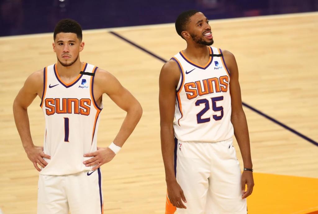 Feb 24, 2021; Phoenix, Arizona, USA; Phoenix Suns guard Devin Booker (1) and forward Mikal Bridges (25) against the Charlotte Hornets at Phoenix Suns Arena. Mandatory Credit: Mark J. Rebilas-USA TODAY Sports