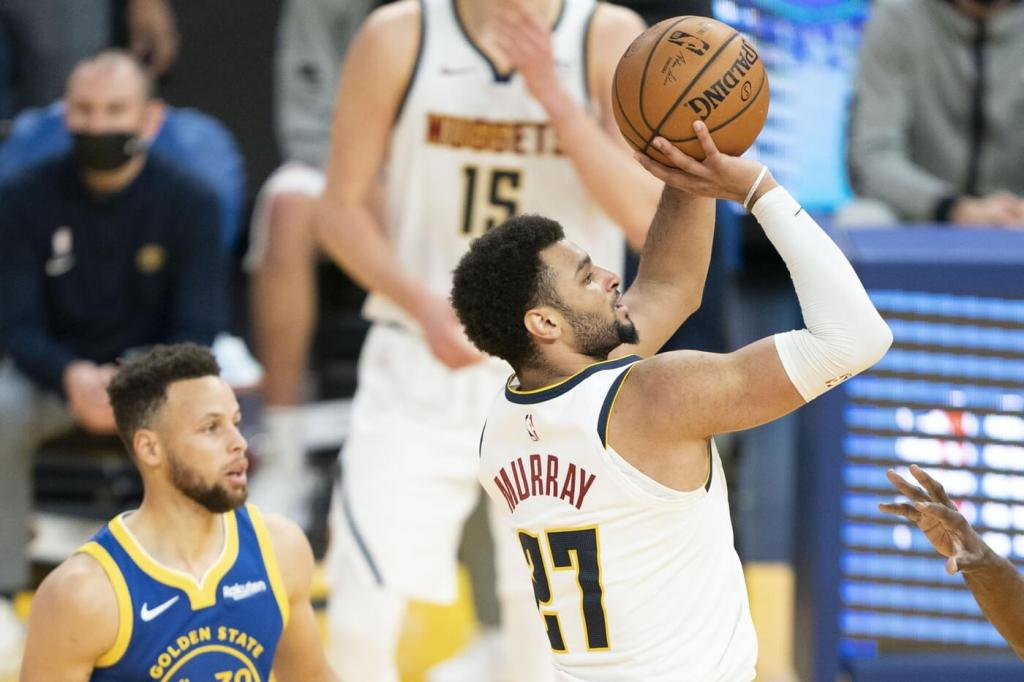 April 12, 2021; San Francisco, California, USA; Denver Nuggets guard Jamal Murray (27) shoots the basketball against Golden State Warriors guard Stephen Curry (30) during the second quarter at Chase Center. Mandatory Credit: Kyle Terada-USA TODAY Sports